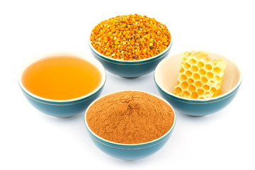 Honey, honeycomb, pollen and cinnamon in bowls