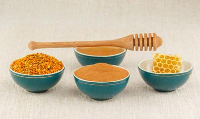 Honey, honeycomb, pollen granules and cinnamon in bowls