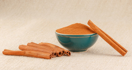 Ground cinnamon in bowl and cinnamon sticks