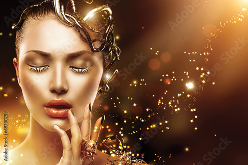 Model girl face with gold skin, nails, make-up and accessories