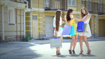 Three beautiful smiling girl on a sunny afternoon to discuss buy