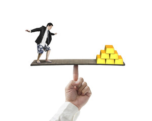 businessman standing on finger seesaw vs stack of gold