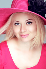 Beautiful blond woman in pink hat with makeup, smiling girl posi