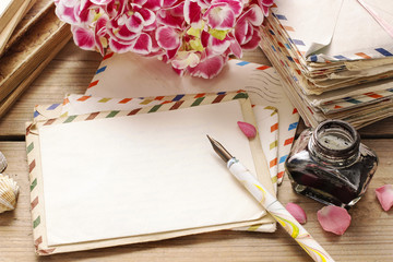 Vintage letters, books and bouquet of pink hortensia flowers
