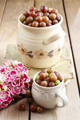 Jug of gooseberries on wooden table