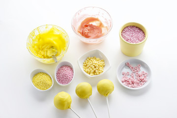Yellow and pink icing and colorful sprinkles