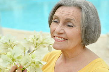 Retired woman posing with flowers