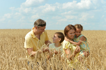 Family standing on wheat field