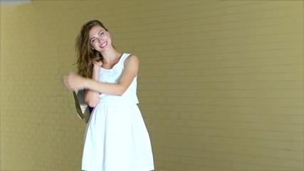 Young cheerful girl shopaholic posing with shopping bag