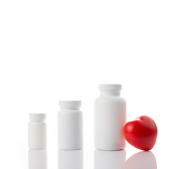Three vitamin bottles with heart on white isolated background