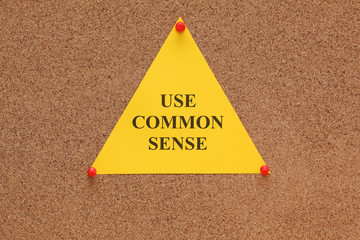"Triangular paper note with the words ""use common sense"""