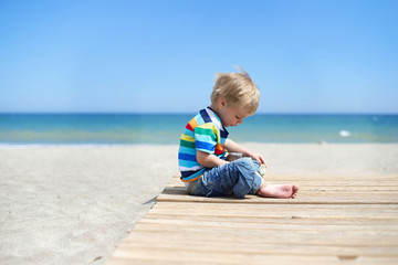 Boy sitting on a wooden walkway on the beach