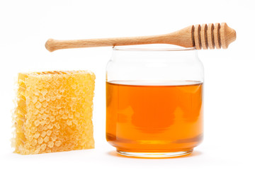 Honey in jar with dipper and honeycomb on isolated background