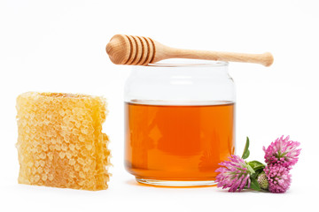 Honey in jar with dipper, honeycomb, flower on isolated backgrou