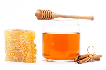 Honey in jar with dipper, honeycomb, cinnamon on isolated backgr