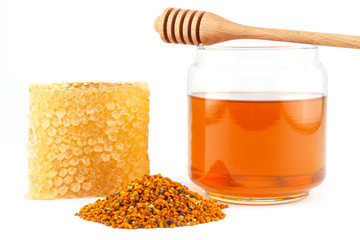 Honey in jar with dipper, honeycomb, pollen on isolated backgrou