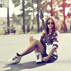 Stylish young woman with electric guitar
