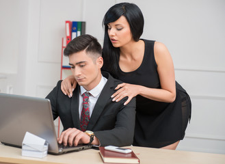 Young businesswoman sitting on table and flirting with working o