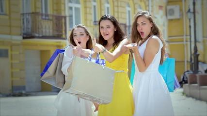 Three cute girls emotionally greet their friends while shopping