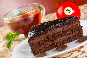 Portion of chocolate cake and cup of tea with fresh mint