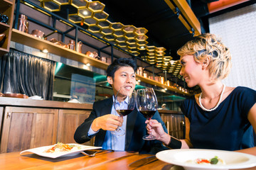 Asian couple toasting with red wine