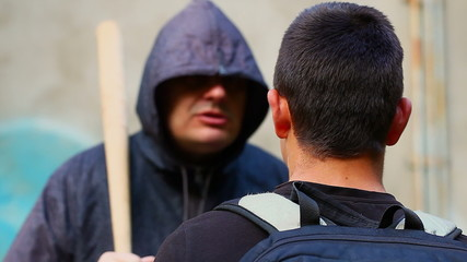 Teenager against aggressive man with a baseball bat at outdoor