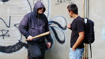 Aggressive man with a baseball bat talking with teenager