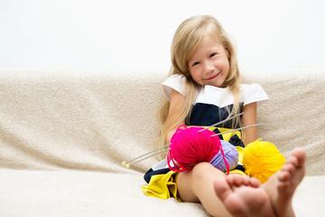 Портрет красивой маленькой девочки с пряжей