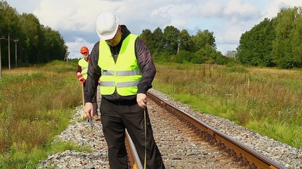 Railroad workers with measuring tape and shovel on a railway