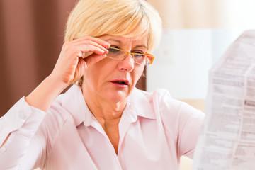 Seniorin liest mit Altersweitsichtigkeit Beipackzettel
