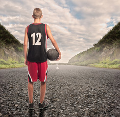 portrait of basketball player standing on a road