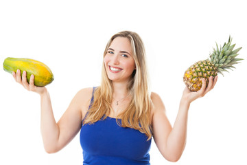 Young healthy beautiful woman with a pineapple and a papaya