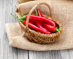 Red chili pepper in a wicker basket with burlap on the wooden ba