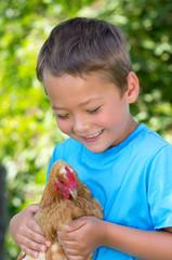 Kleiner Junge hat ein Huhn gefangen