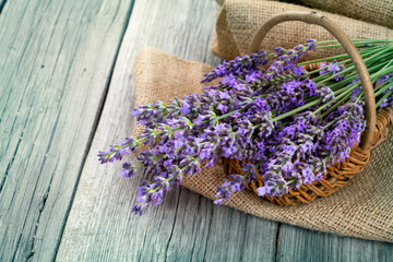 lavender flowers in a basket with burlap on the wooden backgroun