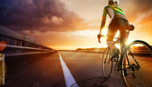 Cyclist riding a bike on an open road to the sunset - 69209683