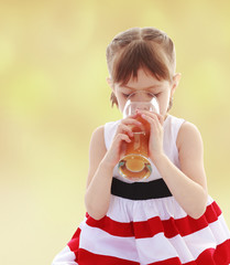 Girl drinking a glass of orange juice.