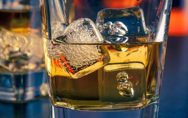 detail of whiskey on bar table with ice