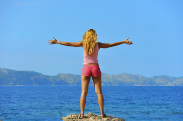 attractive woman standing in front of the sea