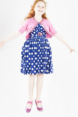 Happy Jumping Red-haired Caucasian Girl In Polka-Dotted Dress