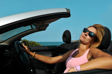 sexy woman with sunglasses driving cabrio sport car in relax
