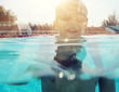 Young boy swimming with half of face under water backlit