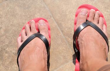 Mens feet in red flip-flops