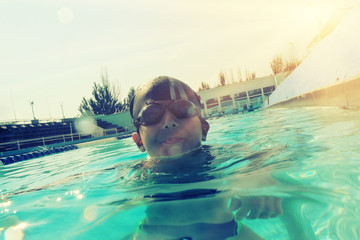 Boy in swimming pool half in water instagram style image