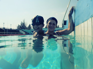Son and mom in pool having fun together