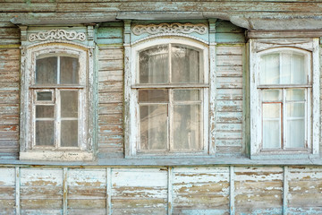 Old windows of obsolete wooden traditional Russian house.
