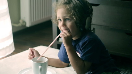 Small boy watching tv and drinking cocoa in the room