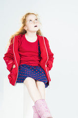 Portrait of Surprised Little Red-haired Caucasian Girl Sitting o