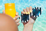 Woman holding sunglasses and sunscreen lotion at the pool