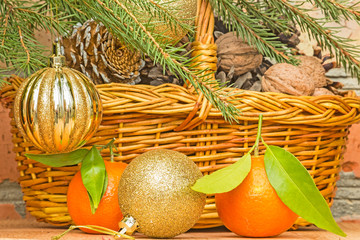 Christmas balls and tangerines on a background of a basket with